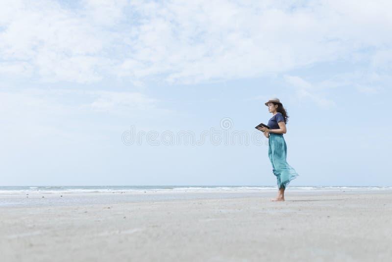 片剂在海滩的用户生活方式 库存照片