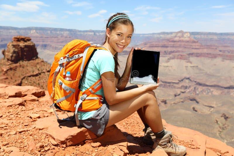 片剂计算机步行在大峡谷的妇女远足者 库存照片