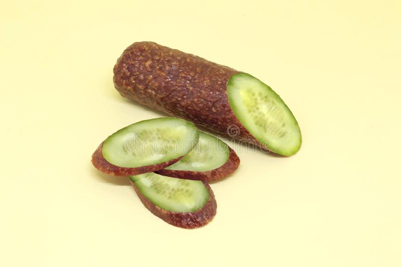 片断和切片熟的干香肠用里面黄瓜 意想不到的食物概念 素食主义者和肉食者的笑话 创造性的想法, 库存图片