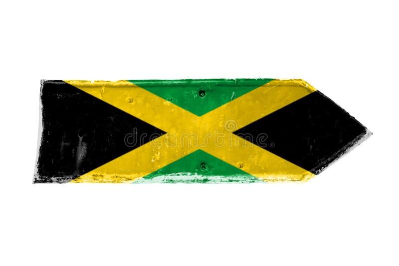 牙买加旗子和颜色绿化,染黄并且染黑在从一块生锈和难看的东西金属铁板材的箭头形状 库存照片