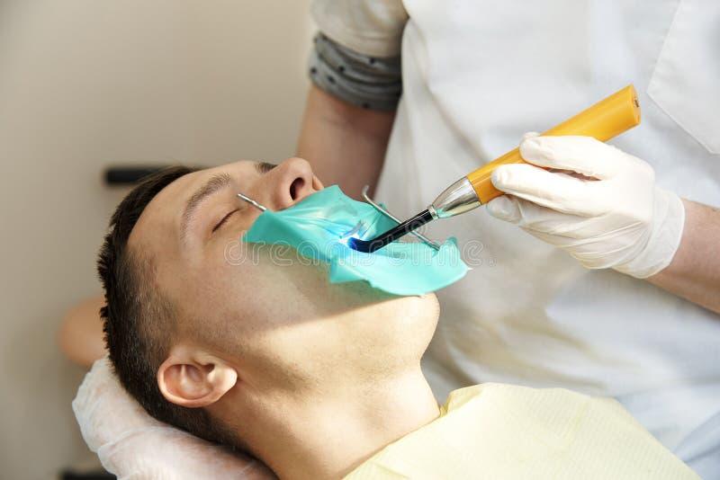 牙医与在耐心` s嘴的一盏牙齿聚化灯一起使用 免版税库存图片