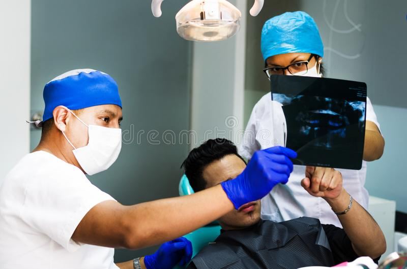牙医医生在人的下颌的X-射线图片的手保留 免版税库存照片
