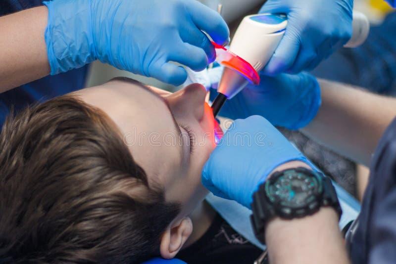 牙医和一种辅助款待一个年轻人的牙 少年在牙科方面 免版税库存图片