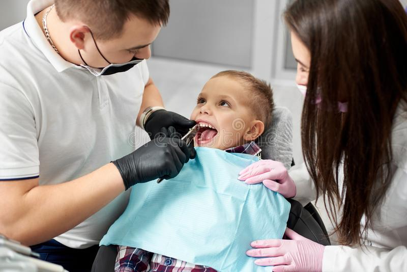 牙医和助理拉扯牙给有镊子的婴孩 库存照片