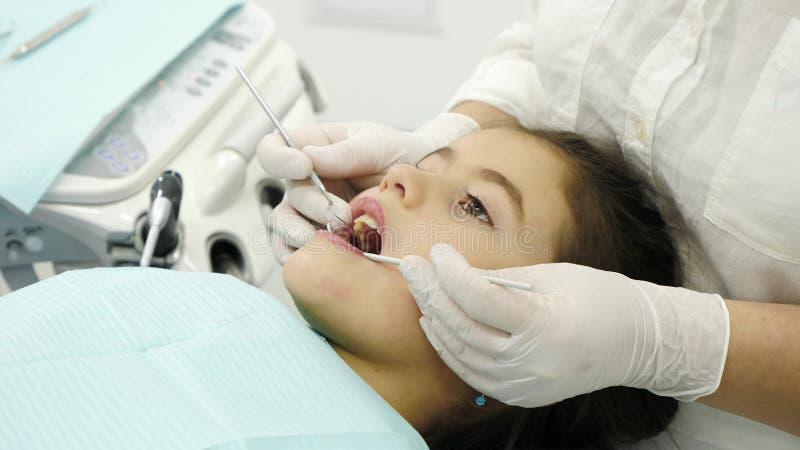 牙医审查小女孩的牙 特写镜头 免版税库存图片