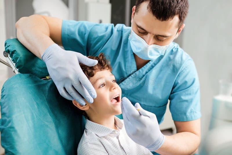 牙医对待一个少年的牙一个牙齿诊所的 免版税库存图片