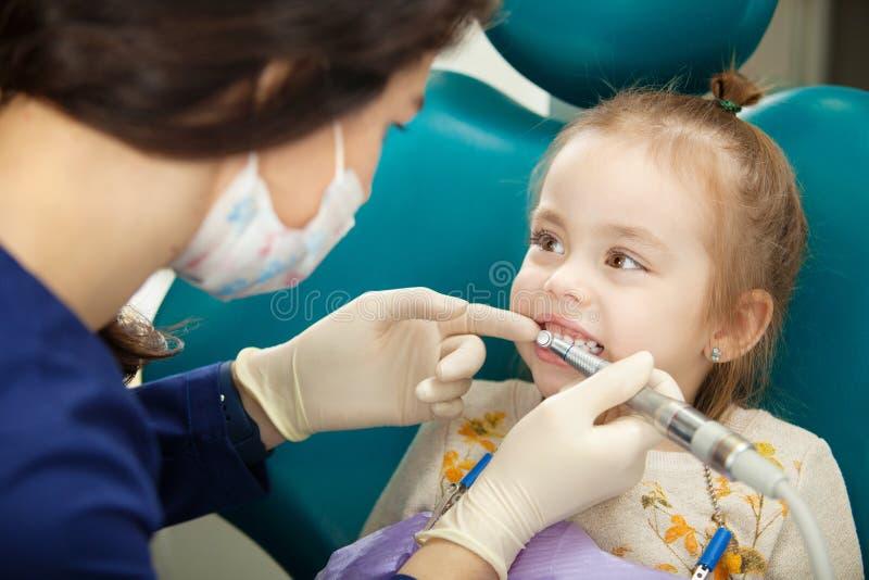 牙医擦亮有现代电工具的childs牙 库存照片