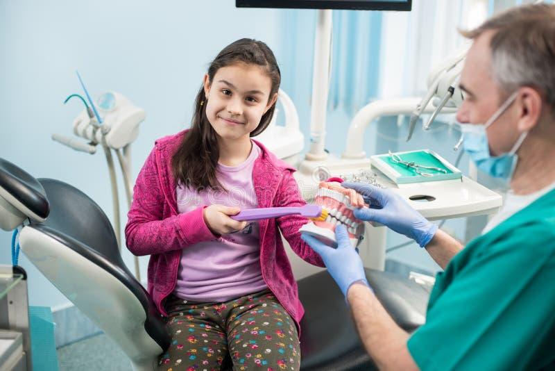 牙医椅子的女孩教育适当牙掠过的由她的小儿科牙医,使用牙齿下颌模型和牙刷 免版税图库摄影