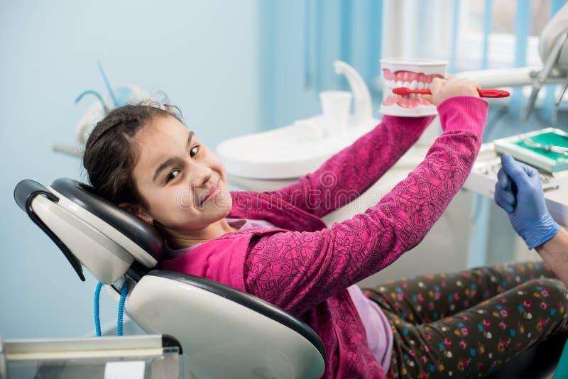 牙医的微笑的女孩主持教育适当牙掠过 免版税库存图片