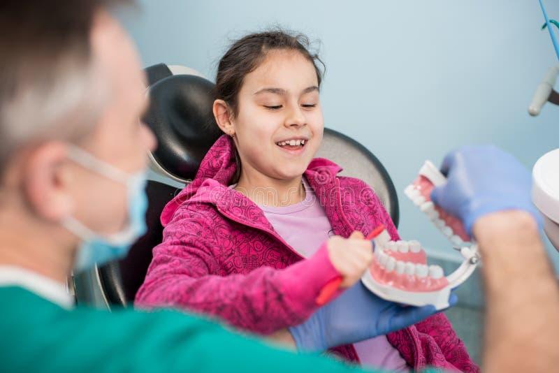 牙医的微笑的女孩由她的小儿科牙医主持教育关于适当牙掠过 免版税图库摄影
