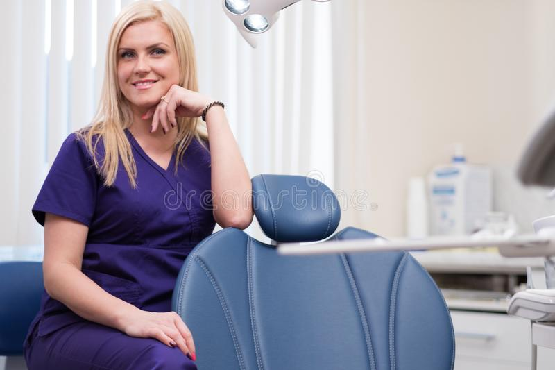 牙医的手术的年轻美丽的白肤金发的妇女牙医 免版税库存照片