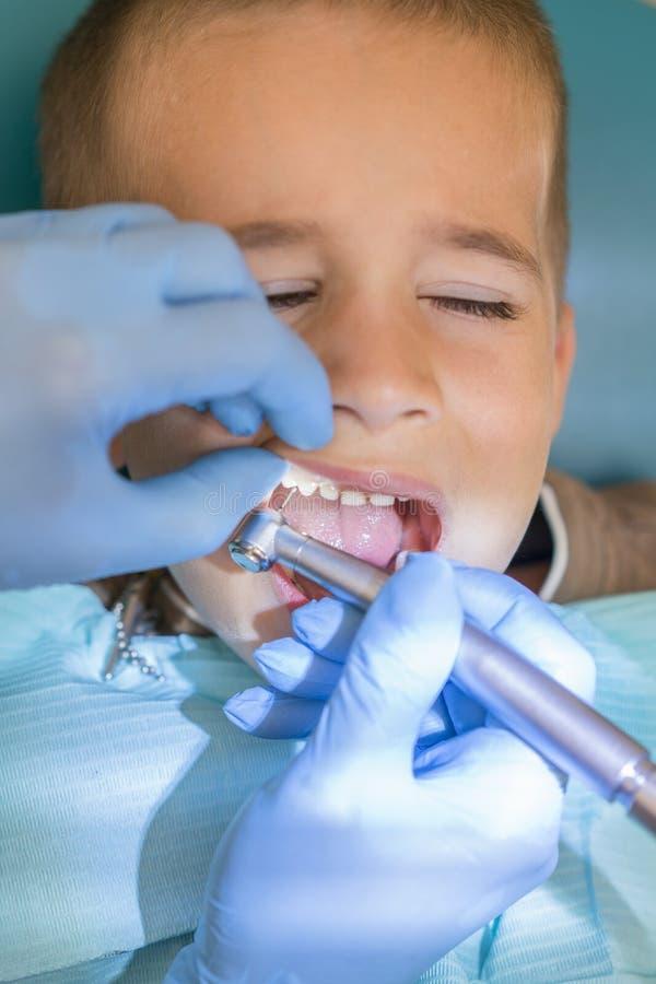 牙医的招待会的一个小男孩一个牙齿诊所的 儿童的牙科,小儿科牙科 一女性stomatologist是 免版税库存图片