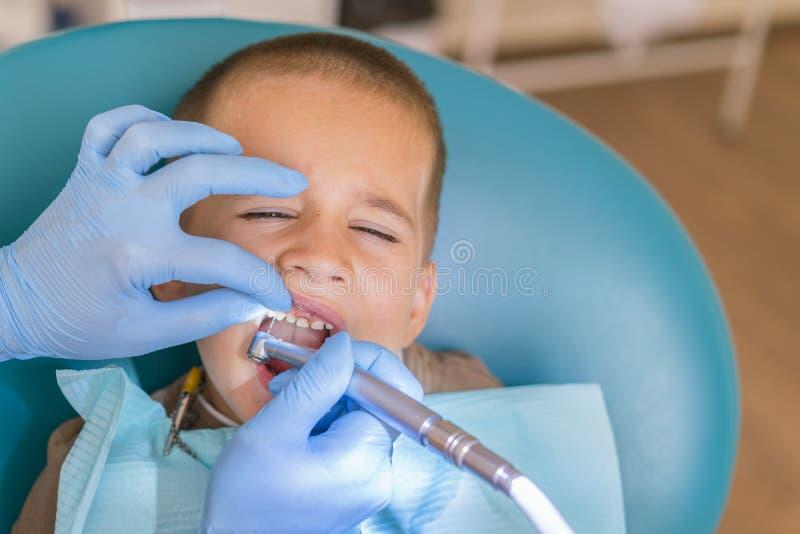 牙医的招待会的一个小男孩一个牙齿诊所的 儿童的牙科,小儿科牙科 一女性stomatologist是 免版税库存照片
