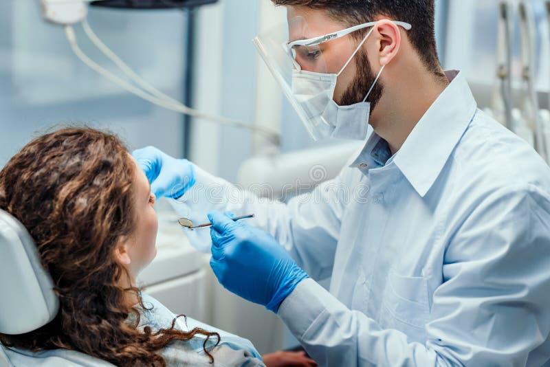 牙医非常小心地检查和修理他的年轻女性患者的牙 o 库存照片