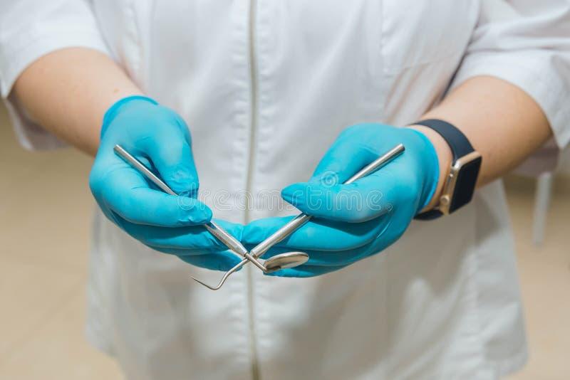 牙医,在白色外套和蓝色手套举行在他的手上工具 免版税库存图片