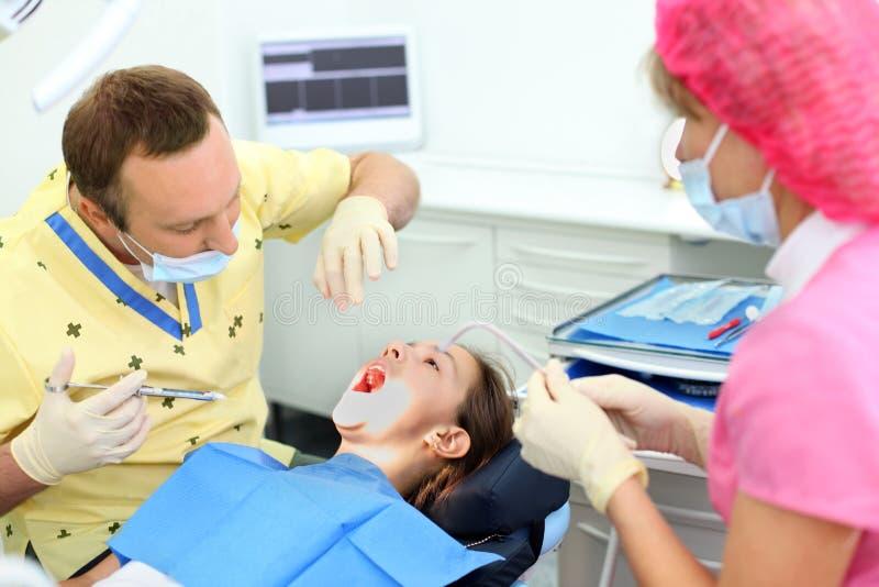 牙科医生准备做射入到女孩开会 免版税库存图片