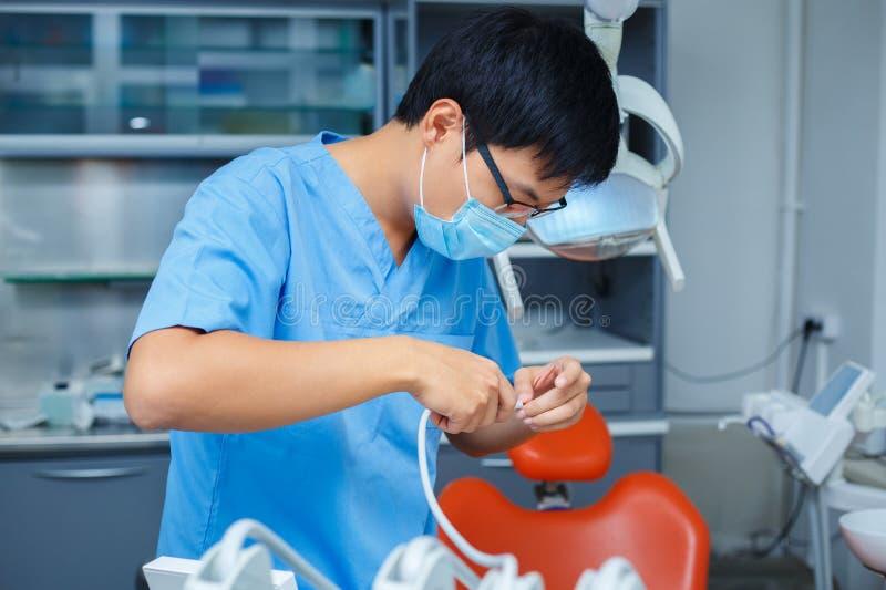 牙科医生在工作 关闭医疗面具的年轻亚裔医生 图库摄影