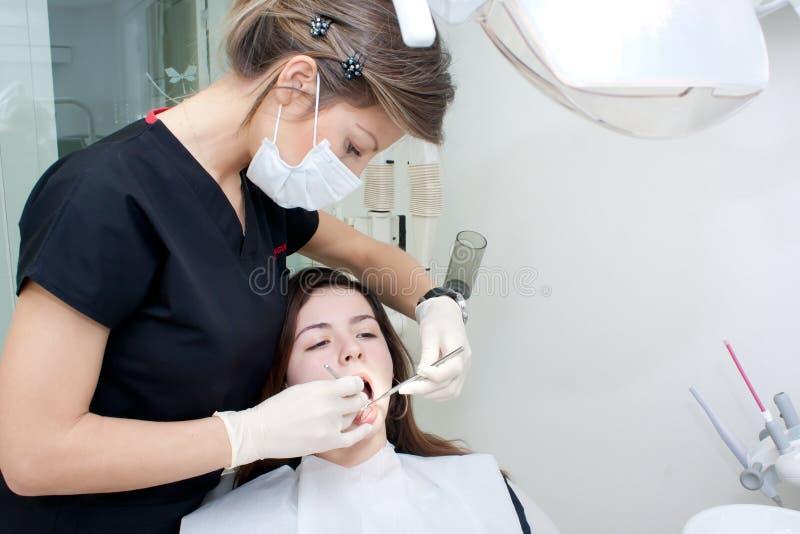 牙科医生她耐心对待 库存照片