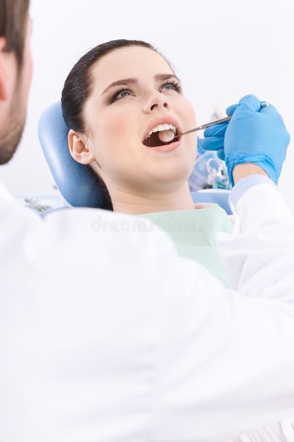 牙科医生检查患者的口腔 免版税库存图片
