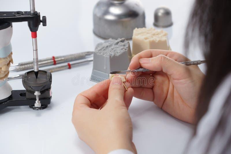牙科技师与发音清楚的人一起使用在牙齿实验室 图库摄影