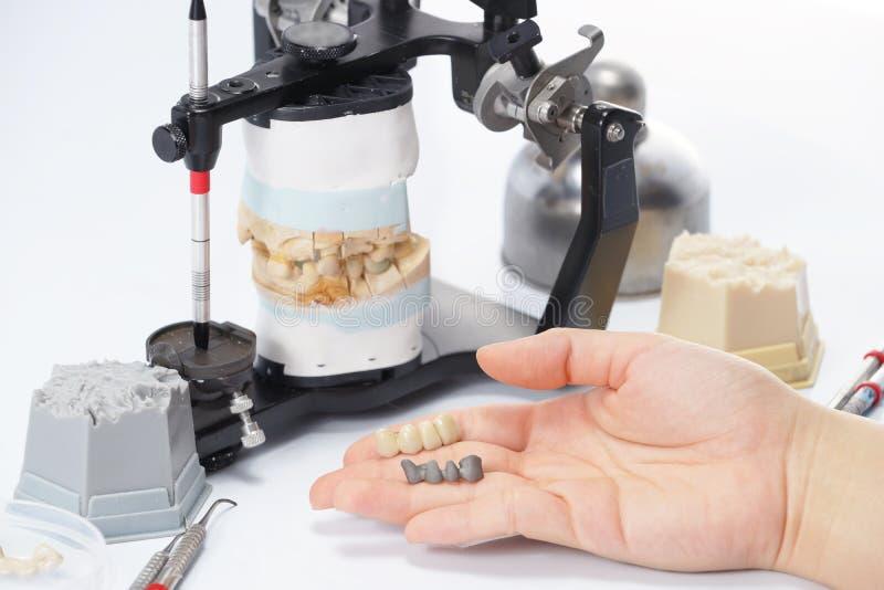 牙科技师与发音清楚的人一起使用在牙齿实验室 免版税库存图片
