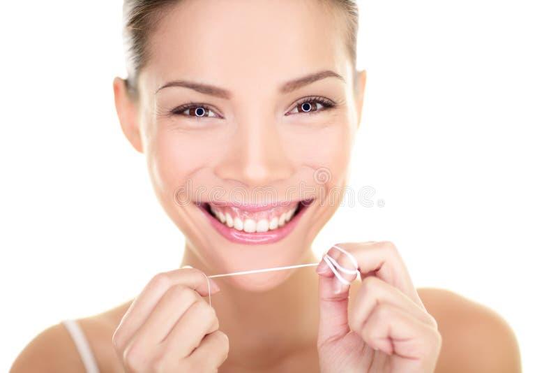 牙线-妇女清洁牙齿的牙微笑 免版税库存图片