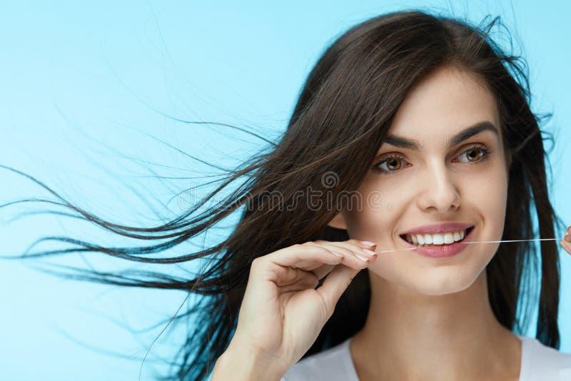 牙齿保护 美丽的妇女清洁牙齿的牙 库存图片