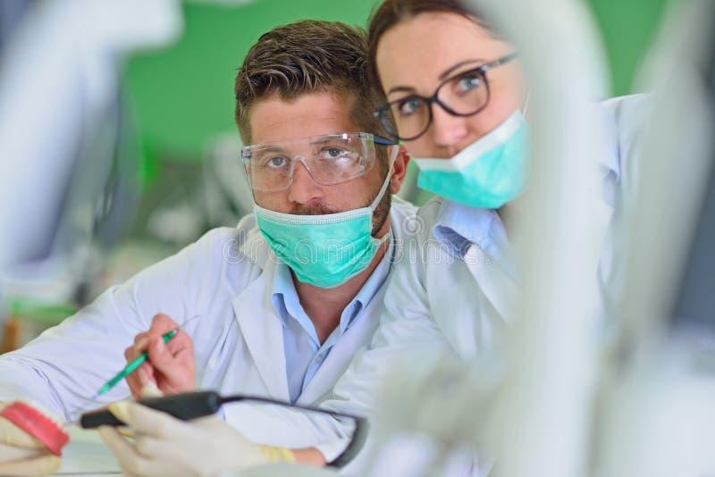 牙齿假肢,假牙,弭补科工作 弭补科手,当工作在假牙时 免版税库存图片