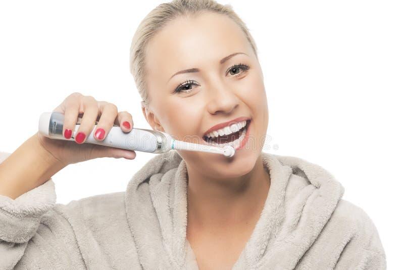 牙齿卫生学概念:愉快微笑白肤金发掠过她的牙Wi 免版税库存图片