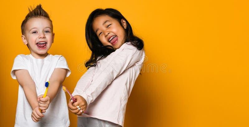 牙齿卫生学 有牙刷的愉快的矮小的逗人喜爱的孩子 库存图片