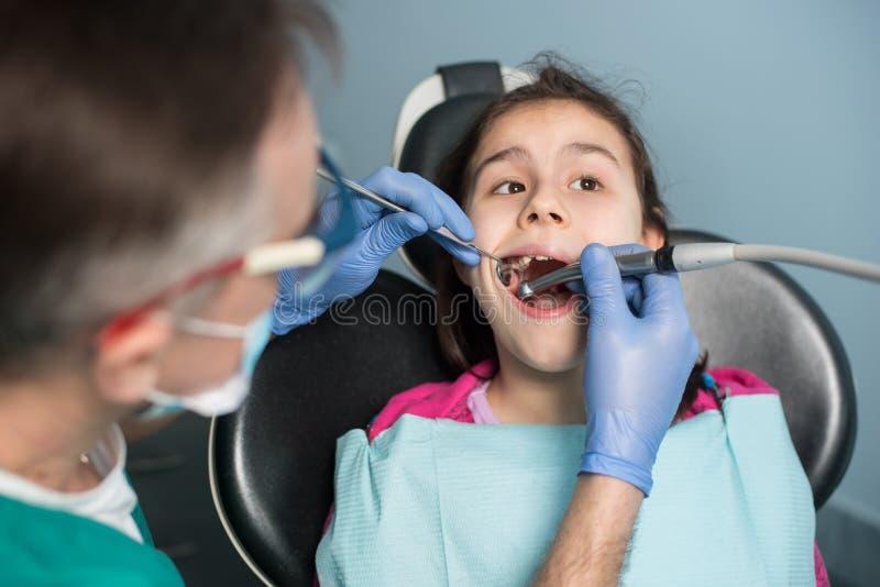 牙齿参观的女孩 对待耐心女孩牙的资深小儿科牙医在牙齿办公室 免版税库存照片