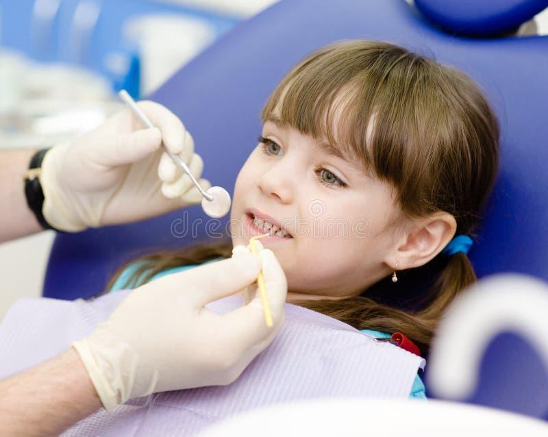 牙齿审查的被给女孩由牙医 免版税库存图片
