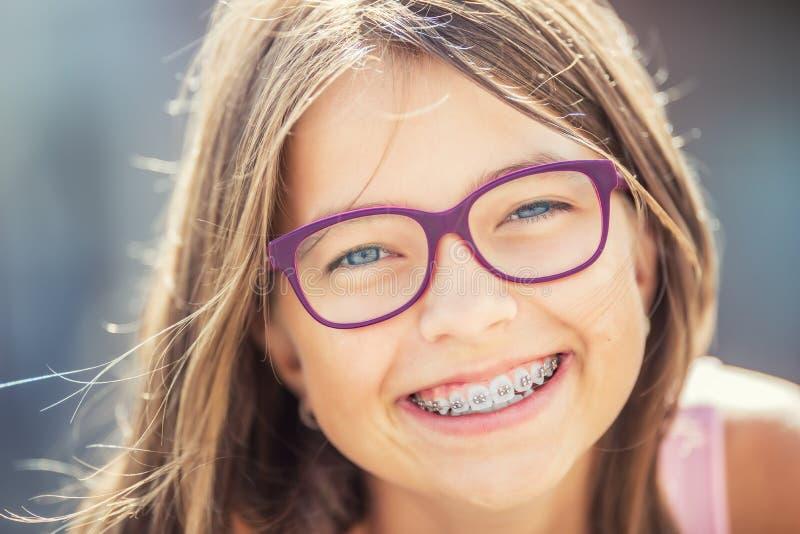 戴牙齿括号和眼镜的愉快的微笑的女孩 年轻逗人喜爱的白种人白肤金发的女孩佩带的牙括号和玻璃 免版税库存图片