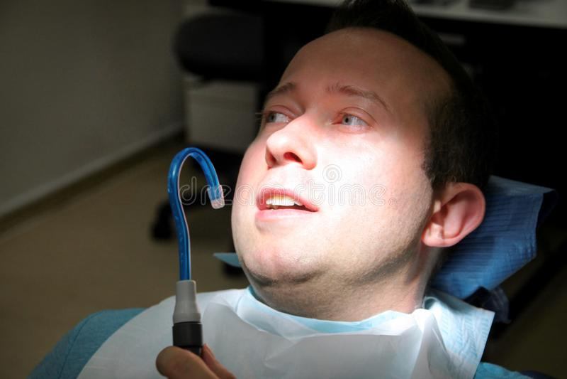 牙齿检查 规则牙齿检查的牙齿男性患者,在牙齿诊所和办公室 有牙齿吸入管的人在嘴 库存照片