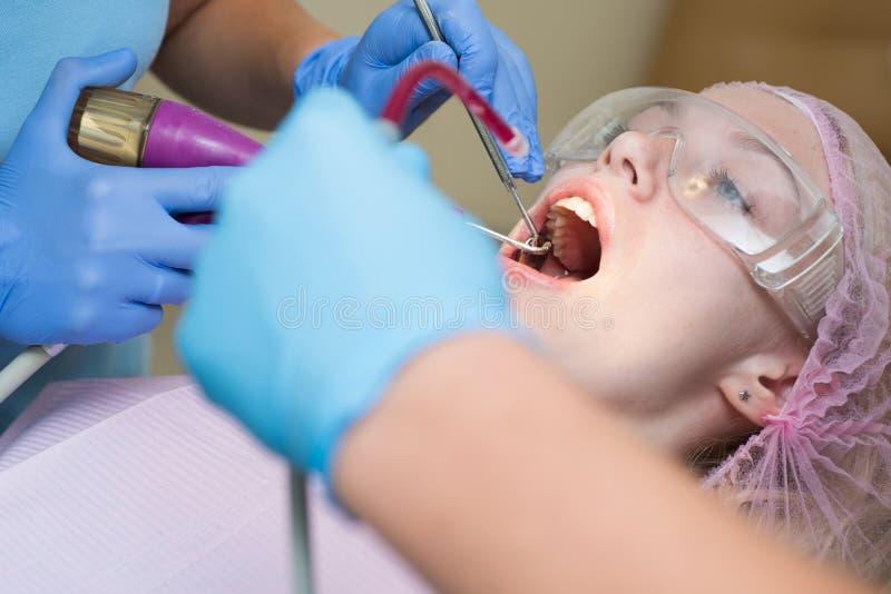 牙齿椅子的美女在显示她完善的平直的白色牙的牙医妇女的考试中 技术 库存图片