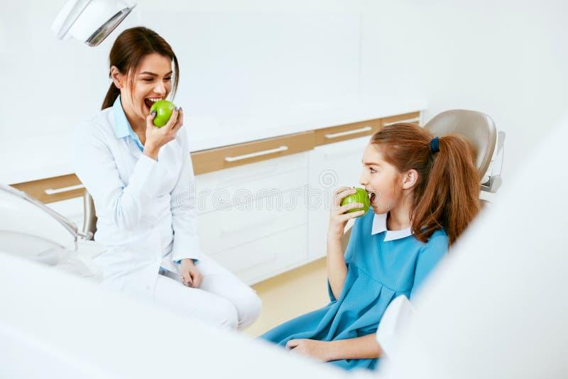 牙齿的诊所 女性牙医和一点耐心吃苹果计算机 免版税库存照片