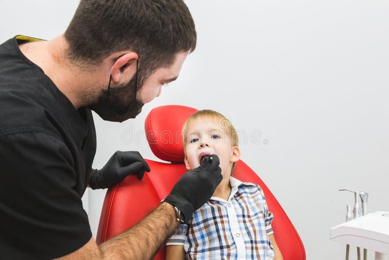 牙齿的诊所 招待会,患者的考试 牙关心 对待小男孩的牙的牙医在牙医办公室 免版税库存照片