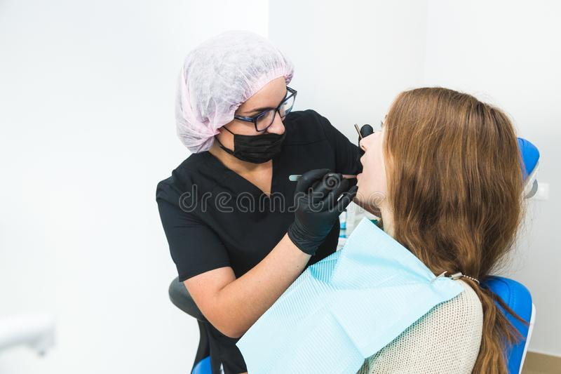 牙齿的诊所 招待会,患者的考试 牙关心 少女由牙医接受一个牙齿检查 库存照片