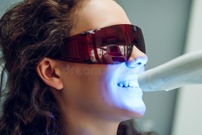 牙齿诊所的女孩患者 有photopolymer构成的牙齿美白紫外灯 o 免版税库存图片
