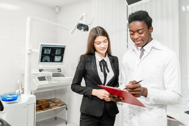 牙齿诊所的妇女患者 年轻非洲男性牙医提出一个诊断和纪录建议 ?? 库存照片