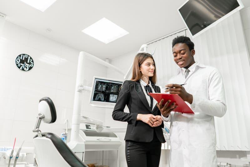 牙齿诊所的妇女患者 年轻非洲男性牙医提出一个诊断和纪录建议 ?? 图库摄影