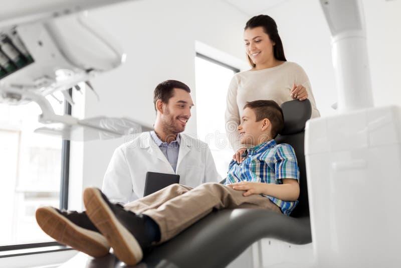 牙齿诊所的母亲和儿子参观的牙医 免版税库存照片
