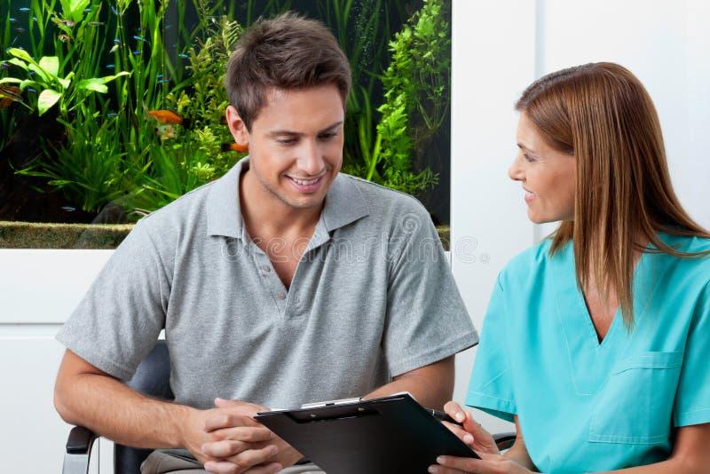 牙齿诊所的医生和男性患者 免版税库存图片