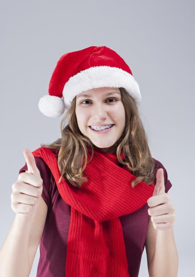 牙齿治疗概念 圣诞老人帽子的愉快的微笑的白种人少年有牙托架的 免版税图库摄影