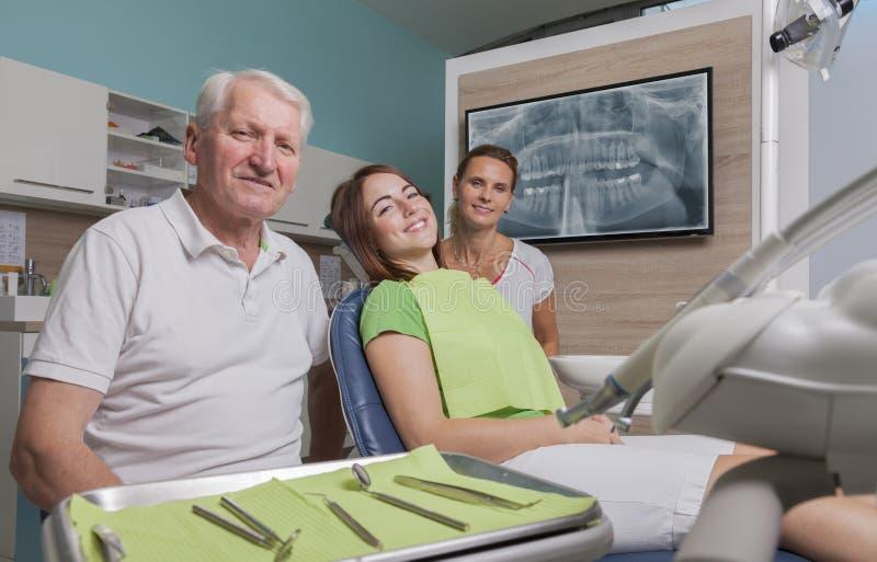 牙医助理和患者在治疗屋子 免版税图库摄影