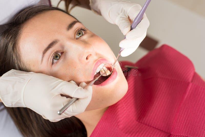牙医审查的女性耐心` s牙在牙医办公室 免版税库存图片