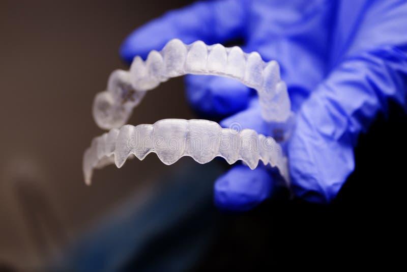 牙医手举行的牙齿畸齿矫正术 免版税库存照片