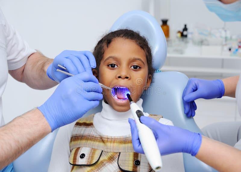 牙医` s椅子的一个深色皮肤的女婴 免版税库存照片