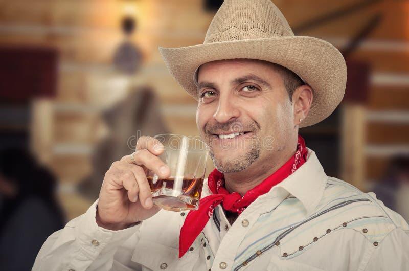 牛仔享用整洁的威士忌酒 图库摄影