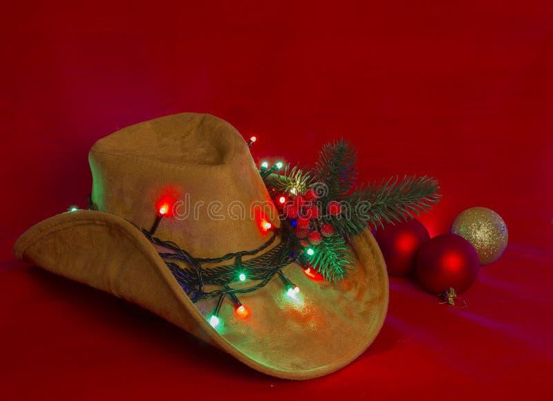 牛仔圣诞节 在圣诞节红色背景的美国西部帽子 库存图片